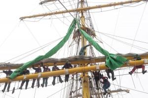 Mitglieder der ehrenamtlichen Crew sind ins Rigg aufgeentert, um die neuen grünen Segel anzunähen.
